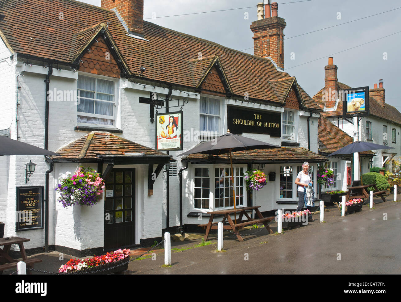 Senior donna lasciando la spalla di montone a Hazeley Heath, un pub vicino Hartley Wintney, Hampshire, Inghilterra, Immagini Stock