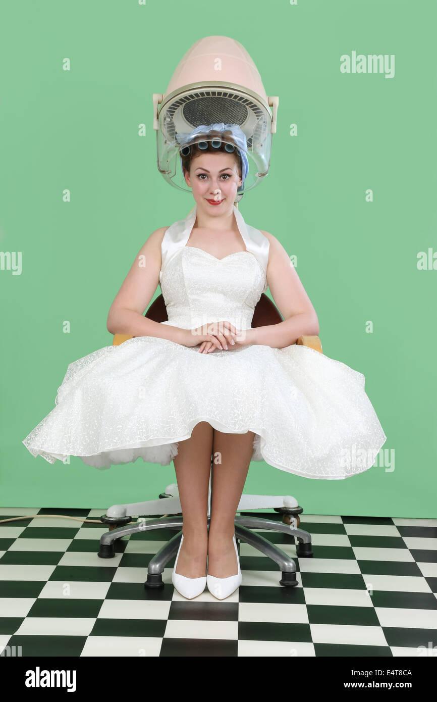 Donna negli anni cinquanta a style abito da sposa seduto sotto un salone vintage asciugacapelli Immagini Stock