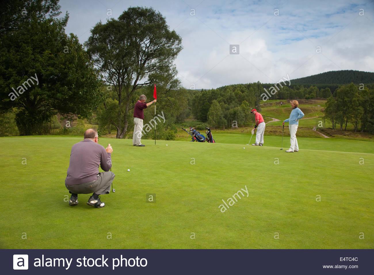 Quattro persone giocare una partita di golf a Carrbridge Golf Club, Cairngorms National Park, Highlands della Scozia. Immagini Stock