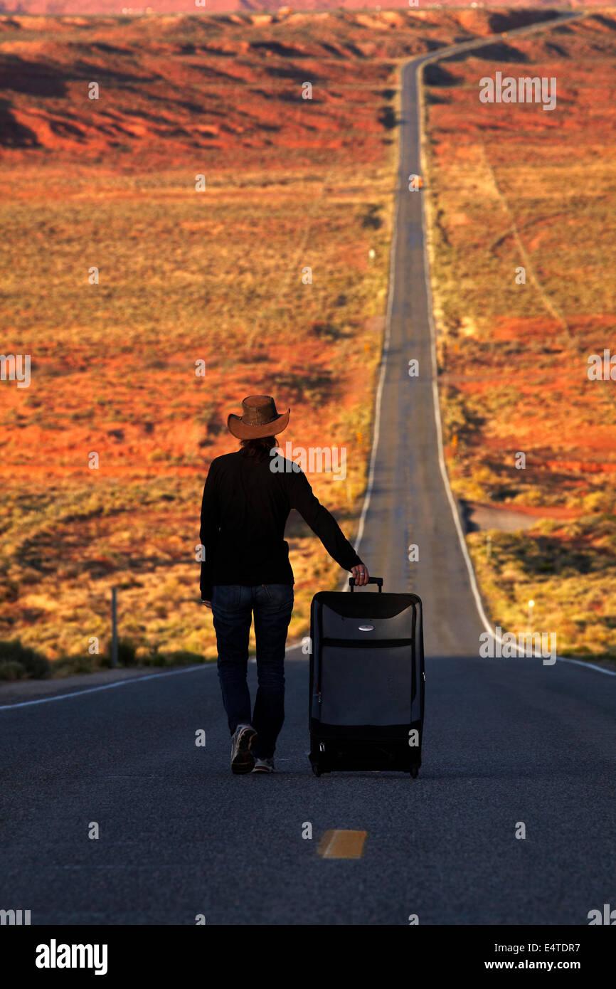 La donna con la valigia NEGLI STATI UNITI. Percorso 163 in direzione Monument Valley Navajo Nation, Utah, vicino Immagini Stock
