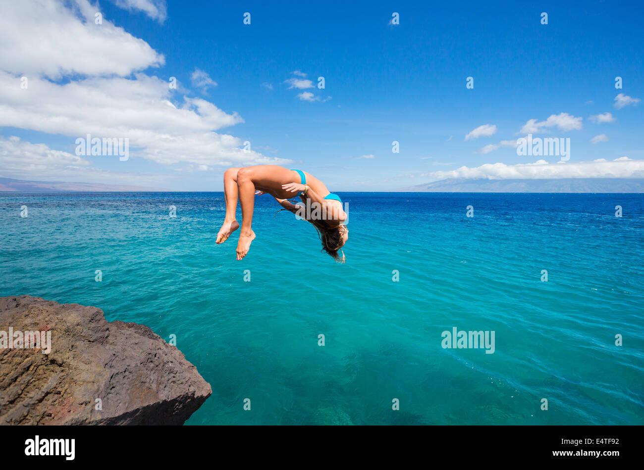 Donna facendo backflip off cliff nell'oceano. Divertimento estivo stile di vita. Immagini Stock