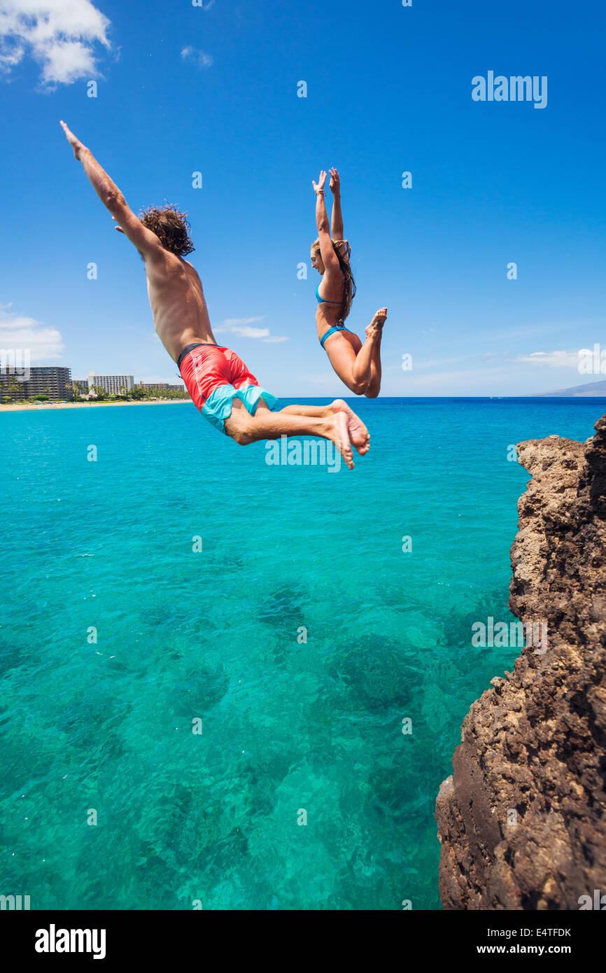 Divertimento estivo, amici cliff jumping nell'oceano. Immagini Stock