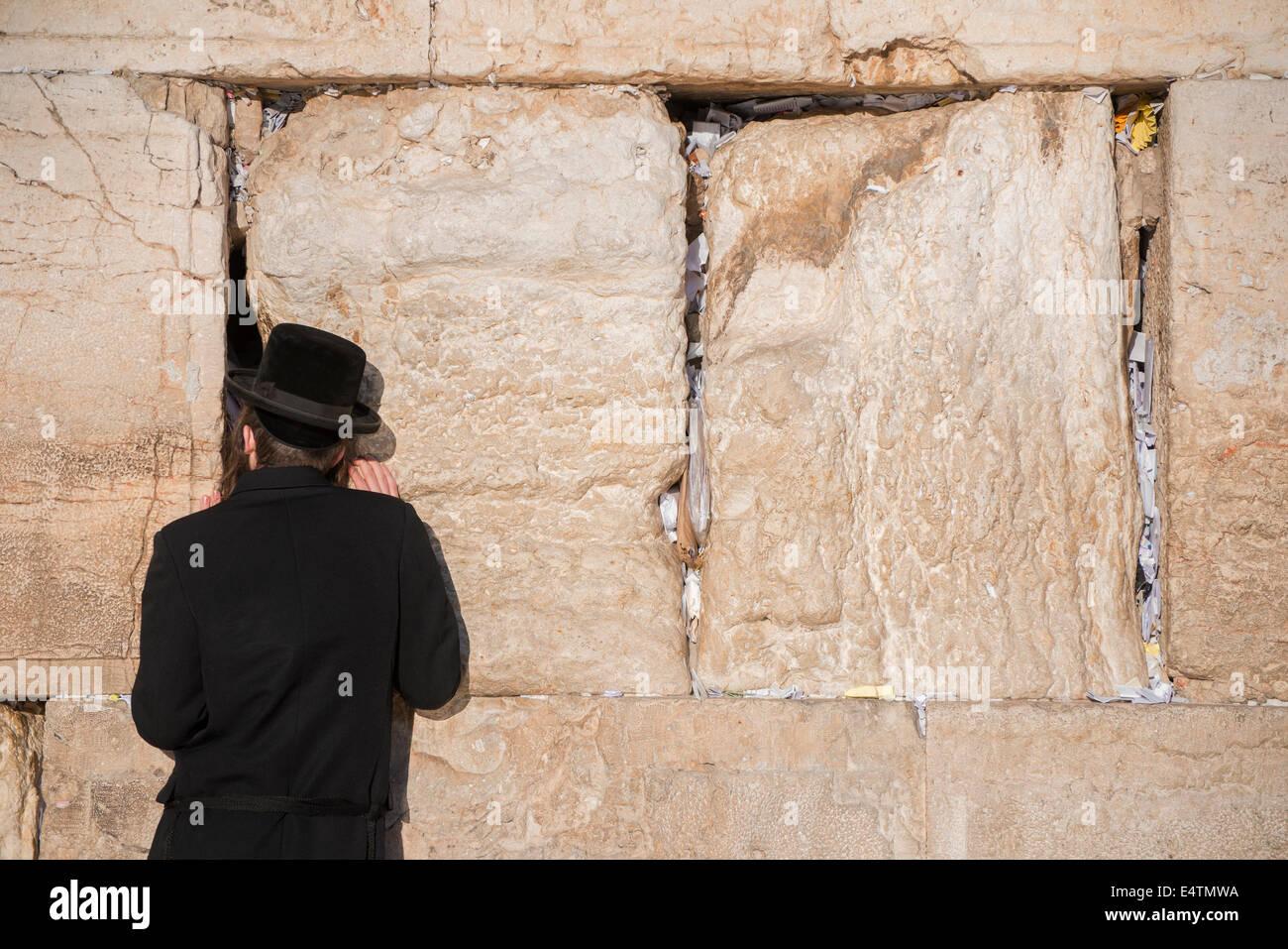 Uomo ebreo prega accanto ad una spaccatura riempita con le lettere contenenti preghiere scritta presso il Muro Occidentale Immagini Stock