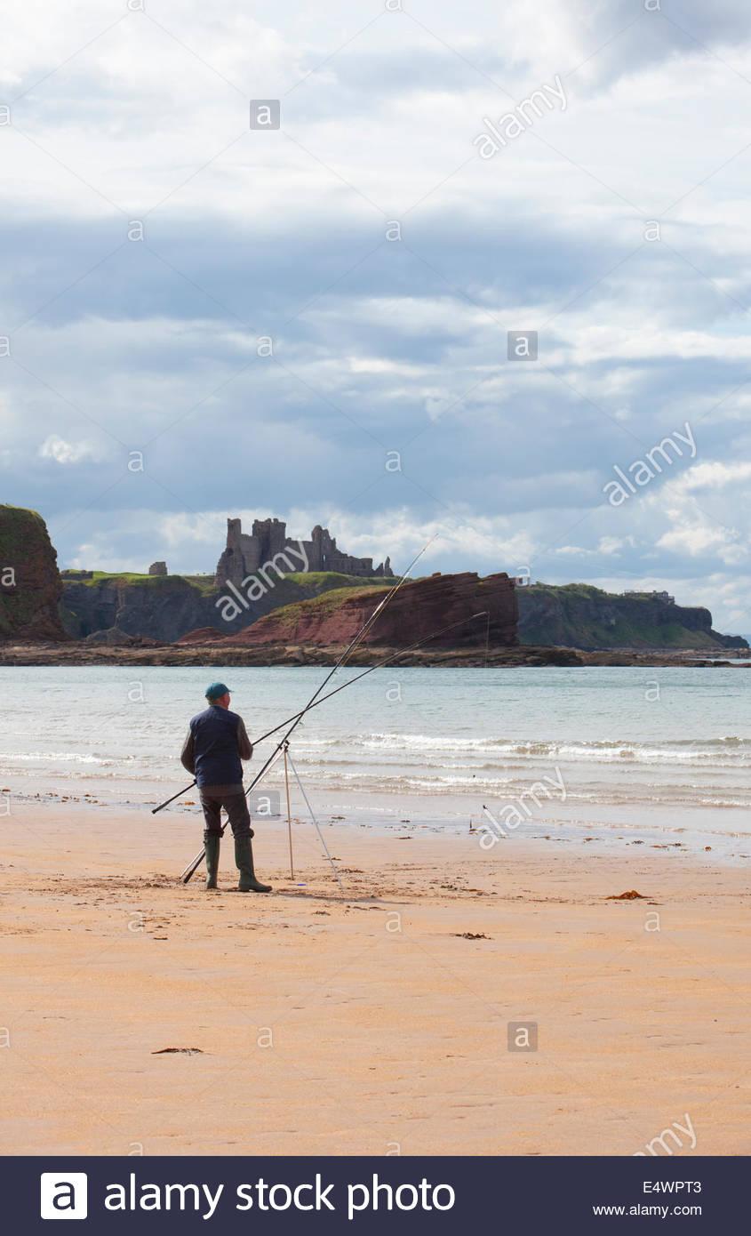 La pesca con lenza in mare dalla spiaggia presso Seacliff con una vista al di là di Tantallon Castle, vicino Immagini Stock