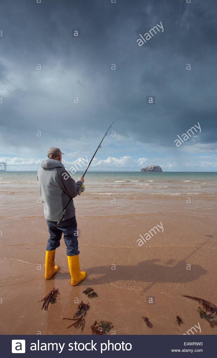 La pesca con lenza in mare dalla spiaggia presso Seacliff con una vista oltre al Bass Rock, vicino a North Berwick, Immagini Stock