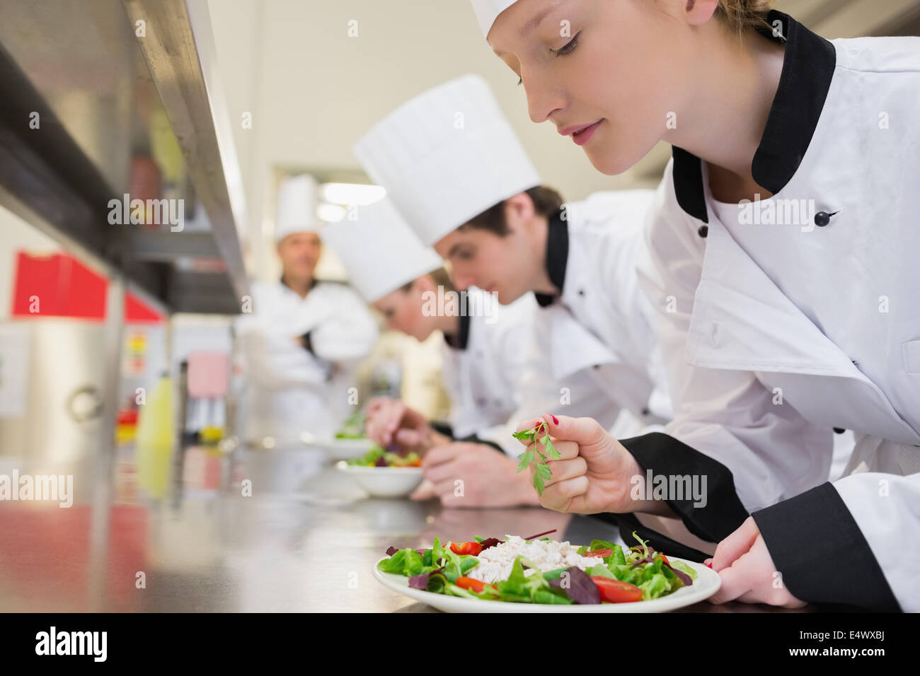 Lo Chef terminato il suo insalata in classe culinaria Immagini Stock