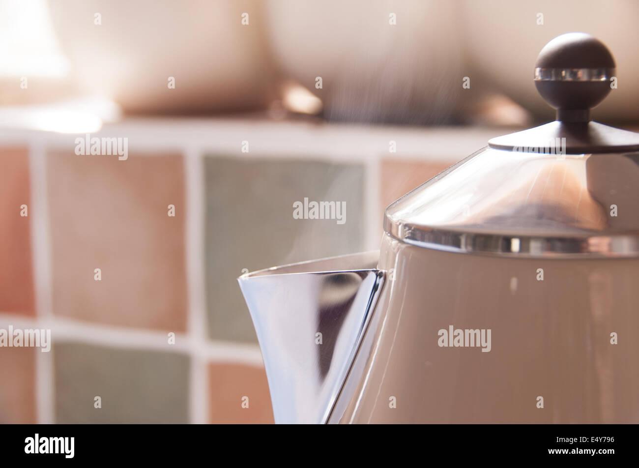 Crema e bollitore metallico ebollizione in una cucina Immagini Stock