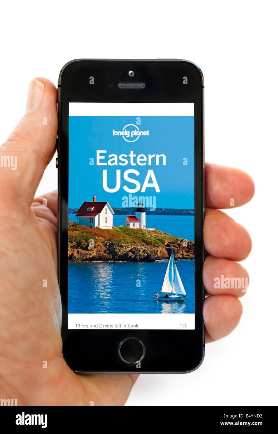 La lettura di una Lonely Planet trave guida su Kindle app su un Apple iPhone 5S Immagini Stock