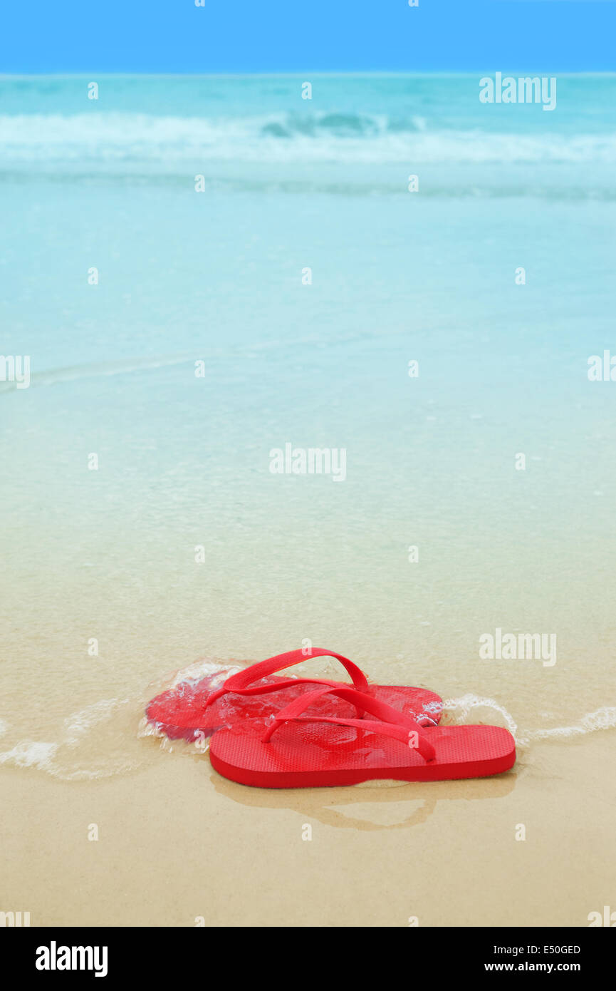 Red flip flop sulla spiaggia Immagini Stock