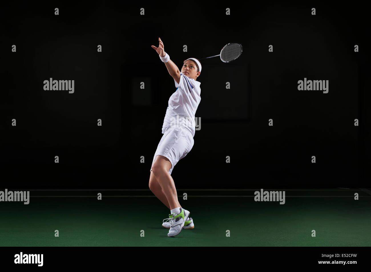 Vista laterale della giovane donna in abbigliamento sportivo giocando badminton isolate su sfondo nero Immagini Stock