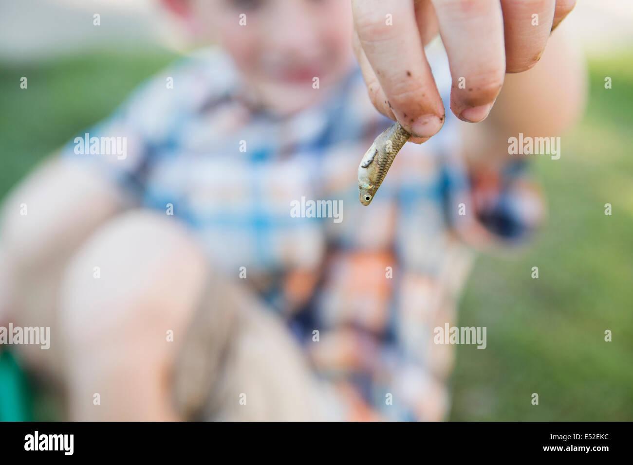 Un giovane ragazzo in possesso di un piccolo pesce in le sue dita. Immagini Stock