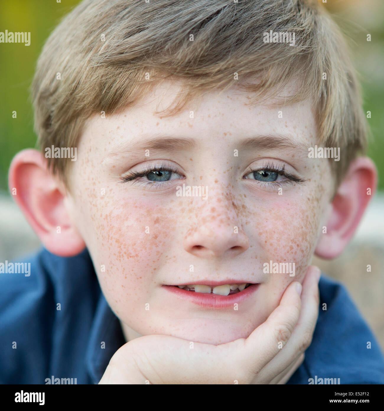 Testa e spalle il ritratto di una giovane ragazzo seduto con il suo mento appoggiato sulla sua mano. Immagini Stock