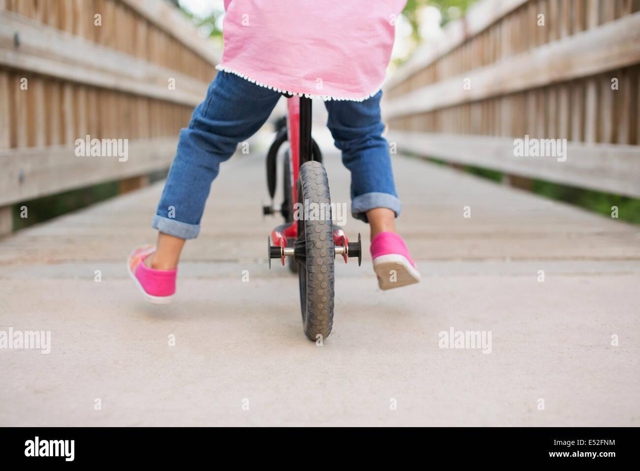 Un bambino in sella ad una bicicletta su una passerella. Immagini Stock