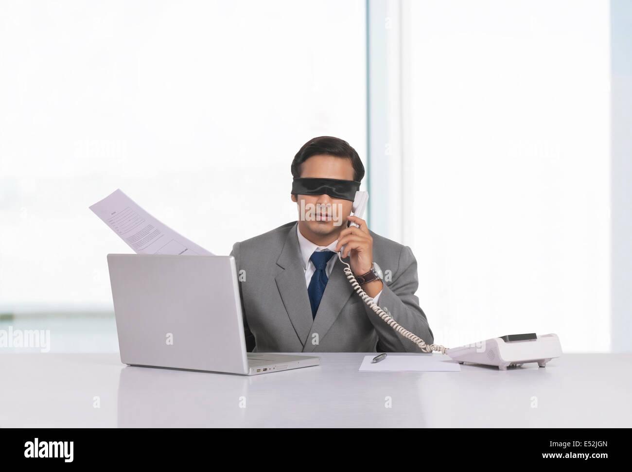 Gli occhi bendati imprenditore lavora alla scrivania in ufficio Immagini Stock