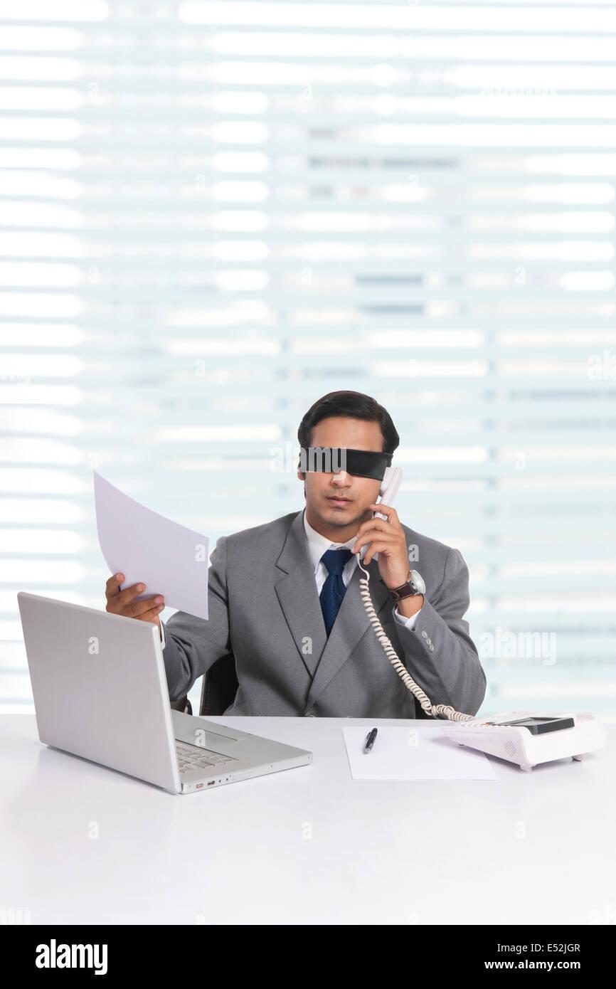 Gli occhi bendati giovane imprenditore lavora alla scrivania in ufficio Immagini Stock