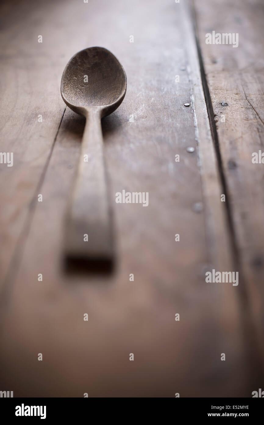 Antique cucchiaio di legno su legno rustico superficie. Foto Stock