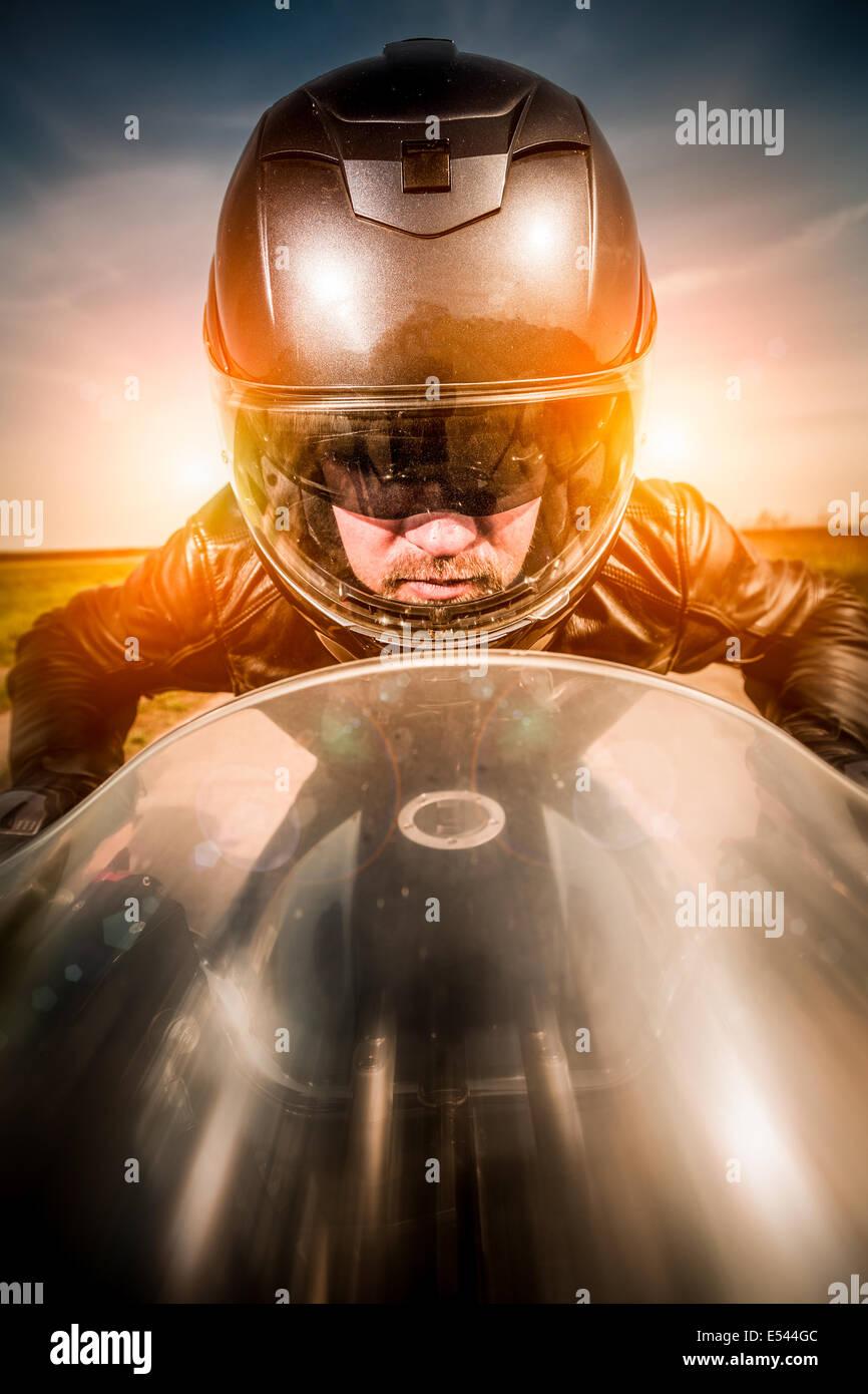 Biker in casco e giacca di pelle racing su strada Immagini Stock