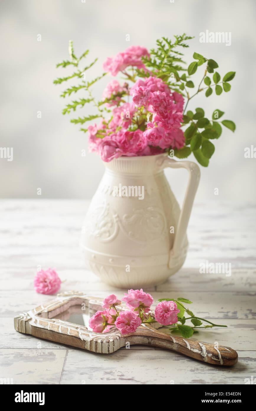 Le rose rosa in vaso antico e a portata di mano lo specchio Immagini Stock