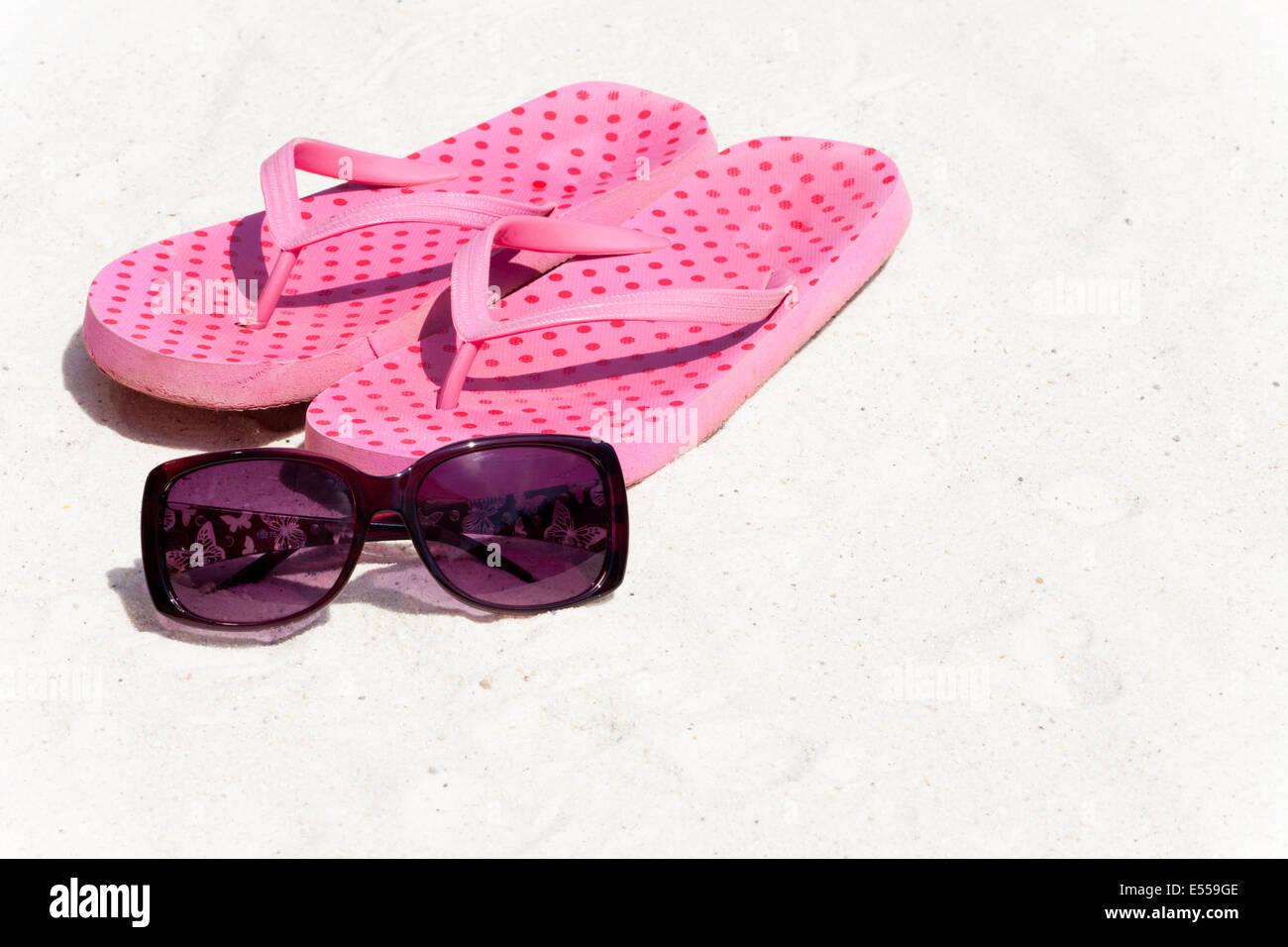 Flip-flops e occhiali da sole nella sabbia sulla spiaggia Immagini Stock
