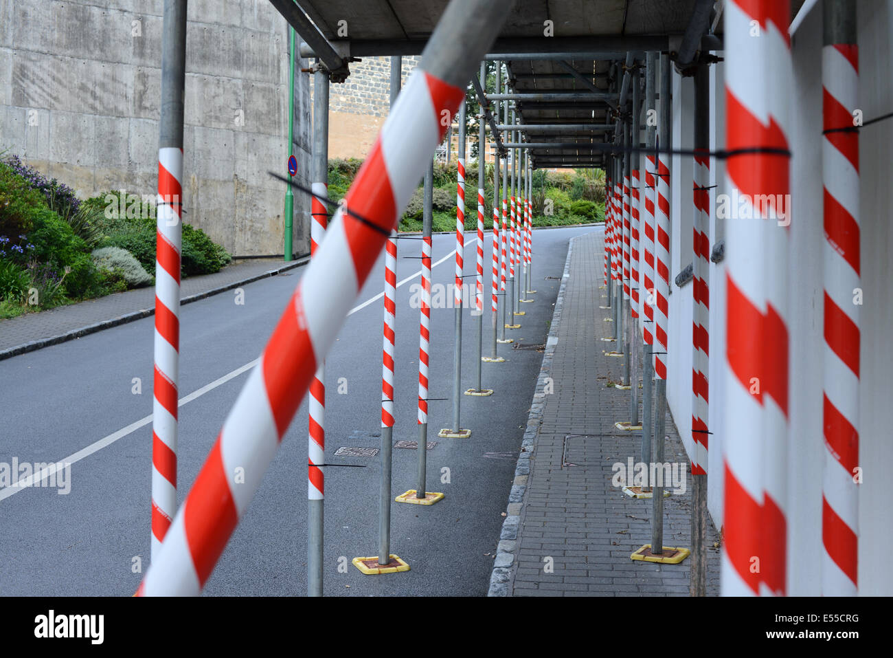 Ponteggio bloccando il marciapiede avvolto in nastro di avvertimento pericolo Immagini Stock