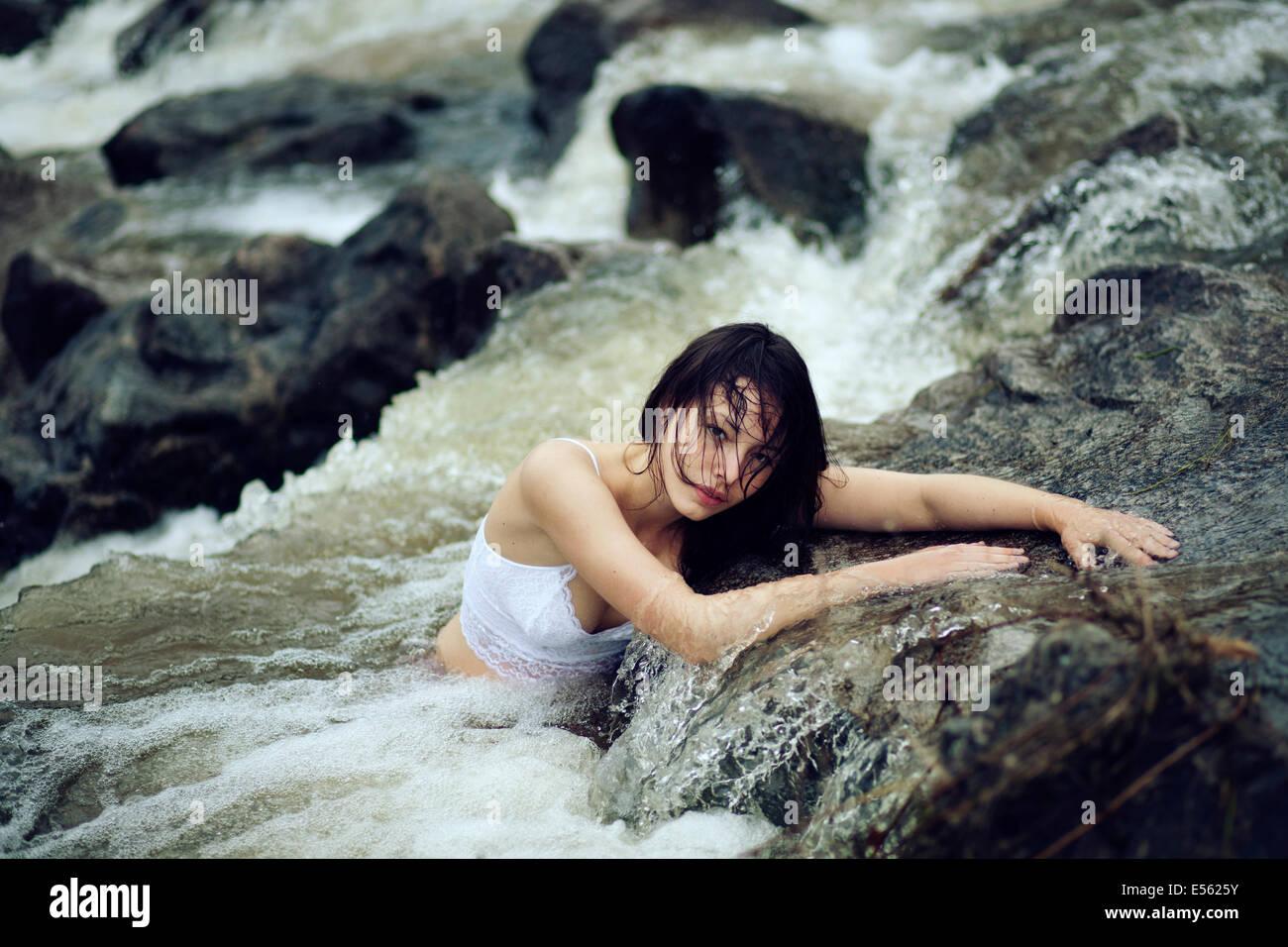 Giovane donna è seduta in un torrente Immagini Stock