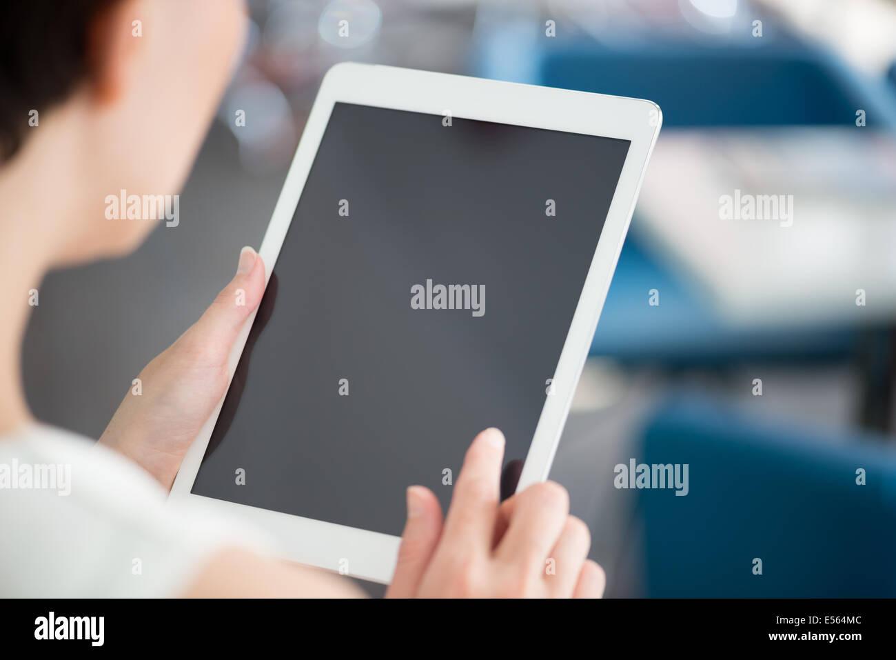 Donna che mantiene e toccante su una moderna tavoletta digitale e guardare su uno schermo vuoto. Immagini Stock