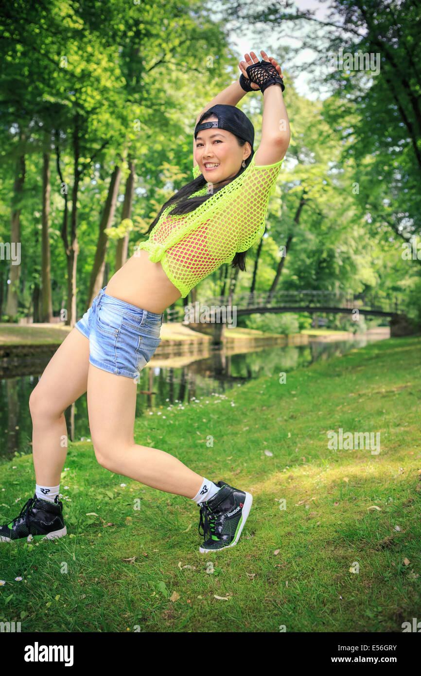 Giovane donna in abiti sportivi in ballo reggaeton o hiphop style nel parco 93f8610c9bbe