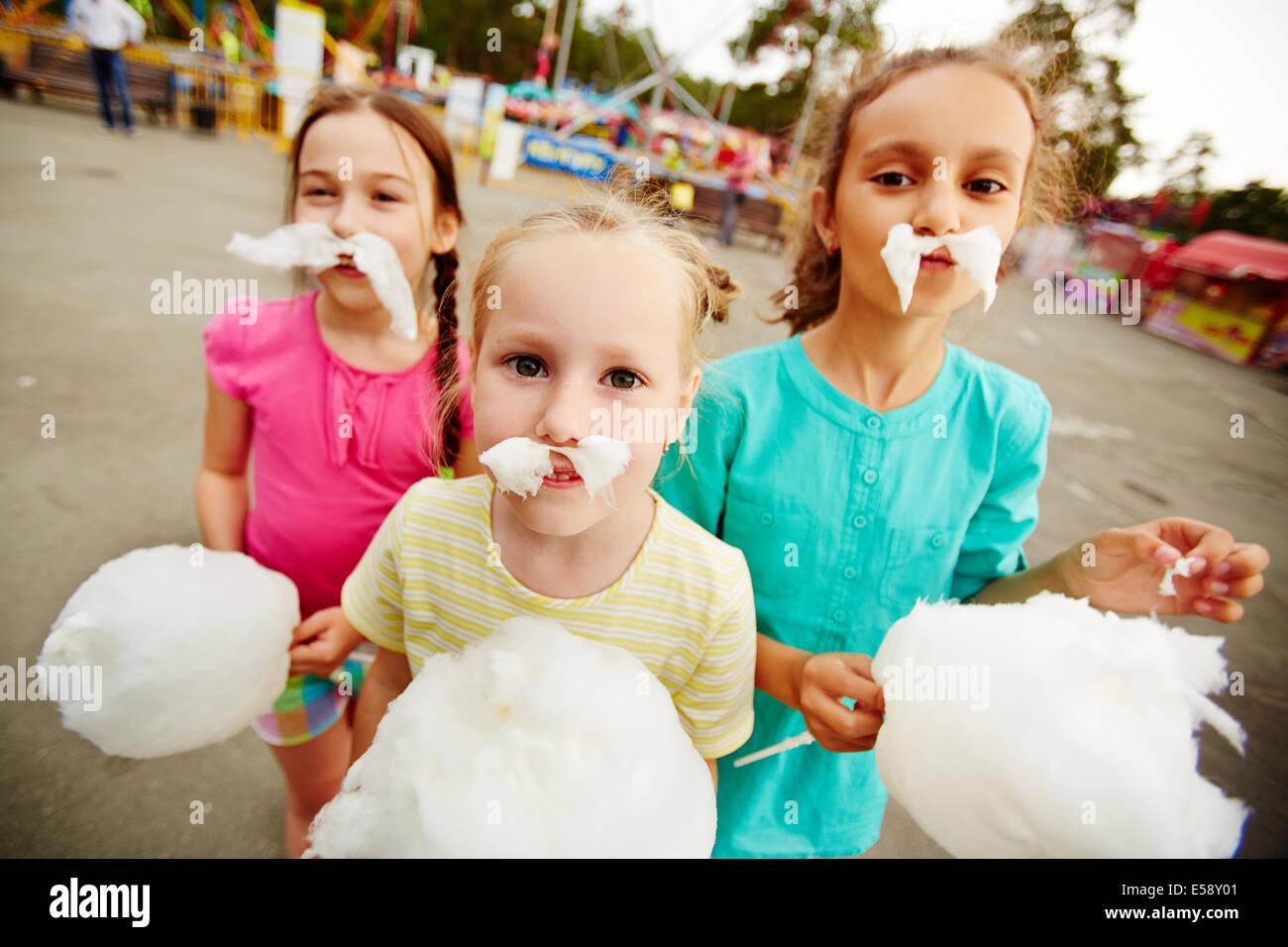 Immagine di ragazze divertente con cotone candy in posa sul parco giochi all'aperto Immagini Stock