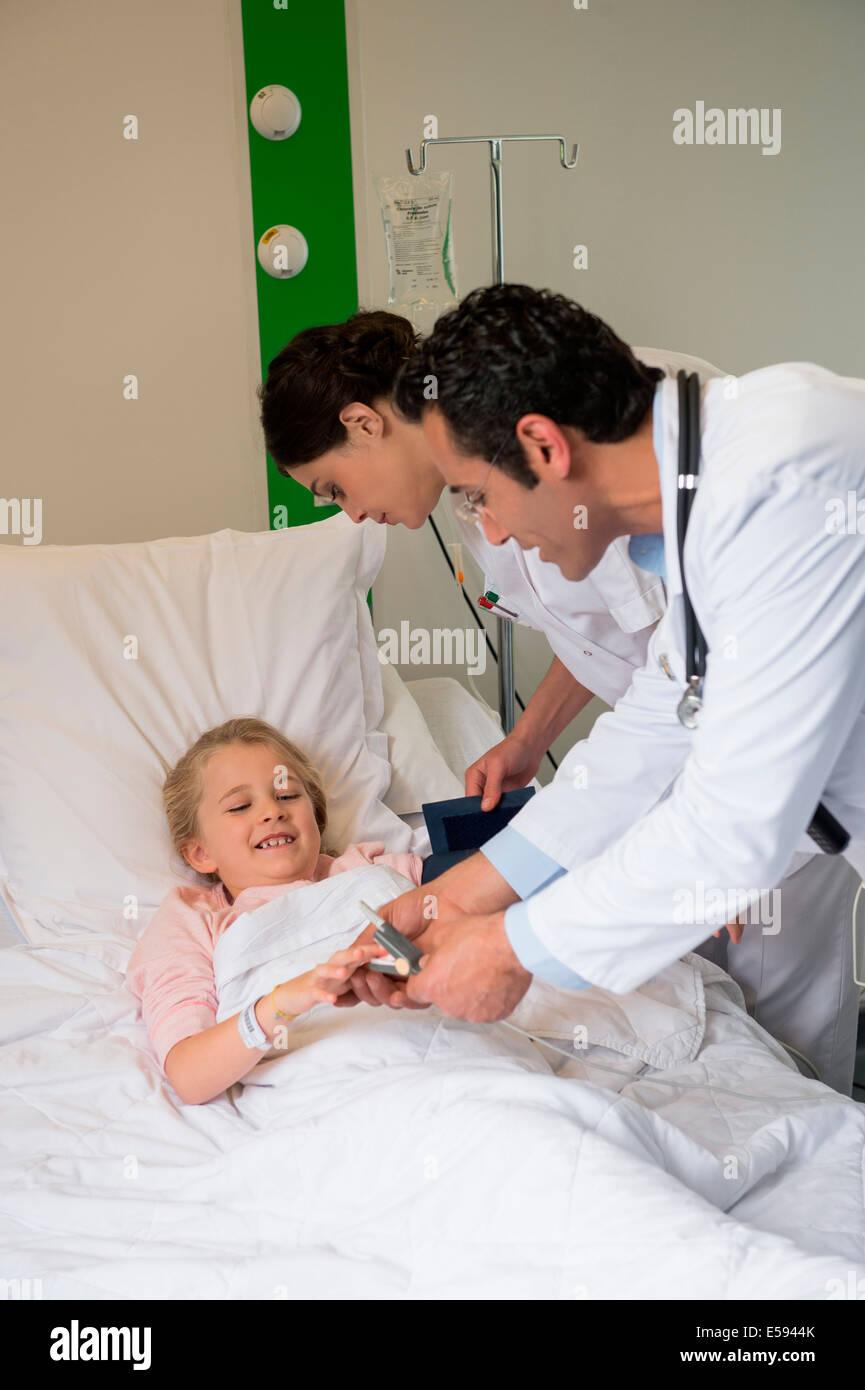 Assistenti medici esaminando a una ragazza paziente nel letto di ospedale Immagini Stock