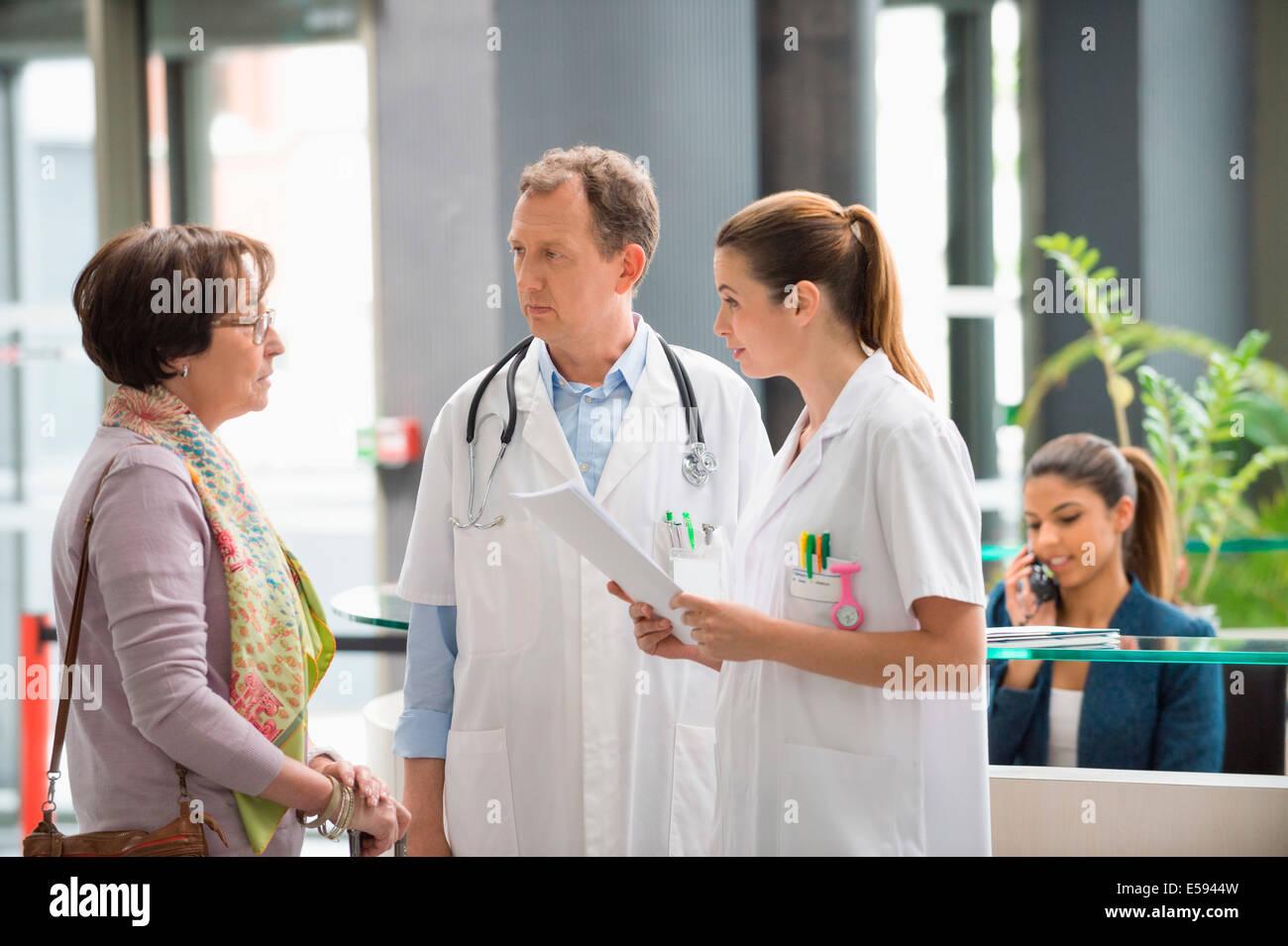 I medici a discutere con il paziente di sesso femminile all'ospedale reception Foto Stock
