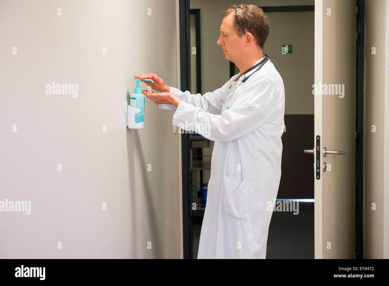 Medico maschio utilizzando igiene lavare a mano nella stanza di ospedale Foto Stock