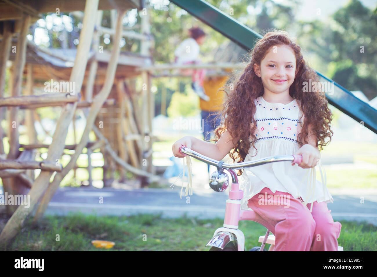 Sorridente ragazza seduta in bicicletta al parco giochi Immagini Stock
