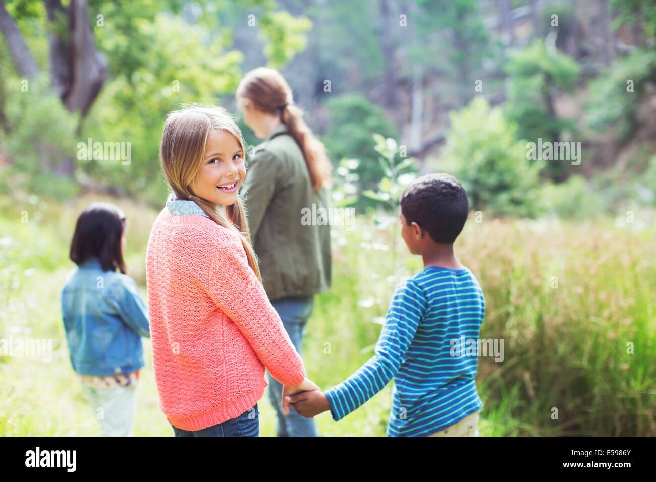 I bambini si tengono per mano nel campo Immagini Stock