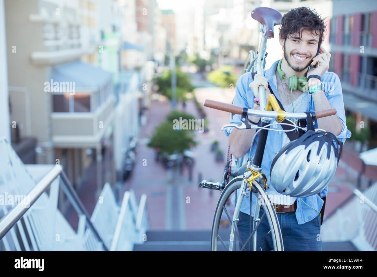 Uomo che porta bicicletta sulle fasi della città Immagini Stock