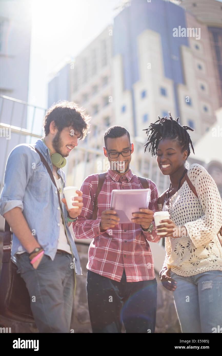 Amici utilizzando la tavoletta digitale sulla strada di città Immagini Stock