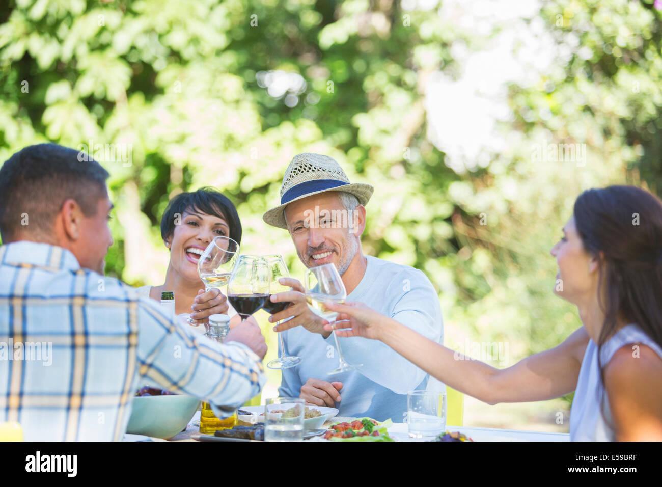 Amici tostare ogni altro a tavola all'aperto Immagini Stock