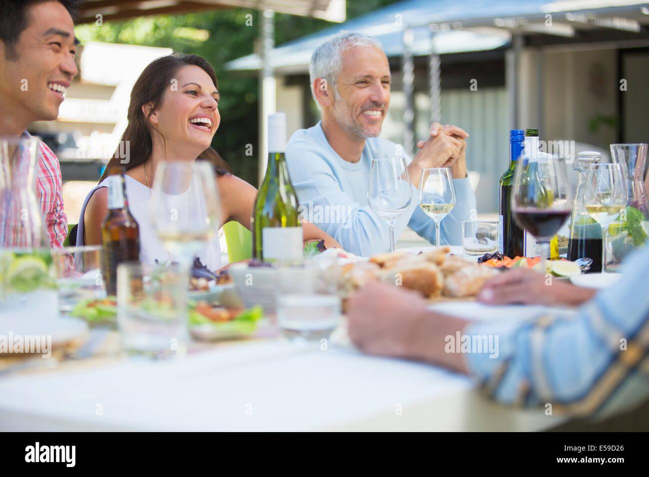 Gli amici di parlare a tavola all'aperto Immagini Stock