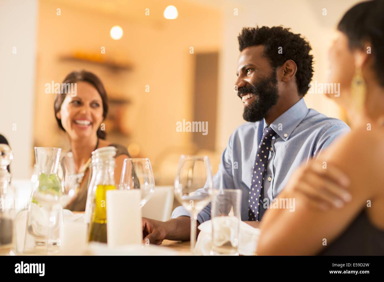 Gli amici di ridere a cena Immagini Stock