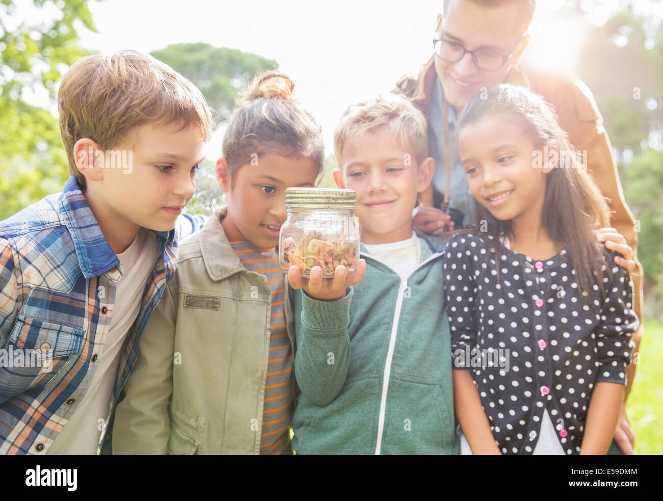 Studente e insegnante di esaminare la presenza di insetti nel vasetto esterno Immagini Stock