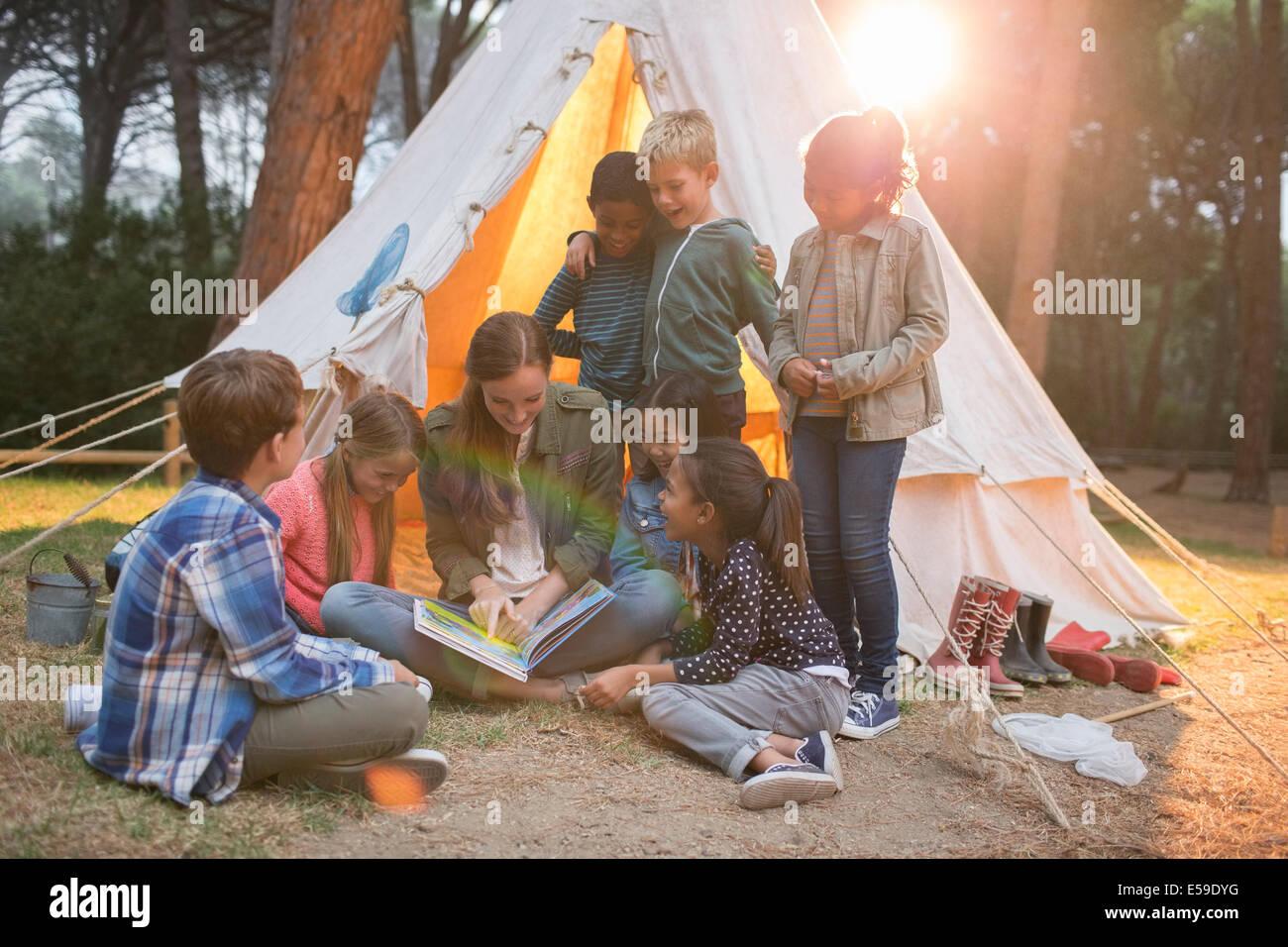 L insegnante e gli studenti lettura al campeggio Immagini Stock