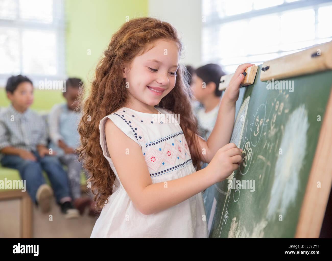 Studente disegno sulla lavagna in aula Foto Stock
