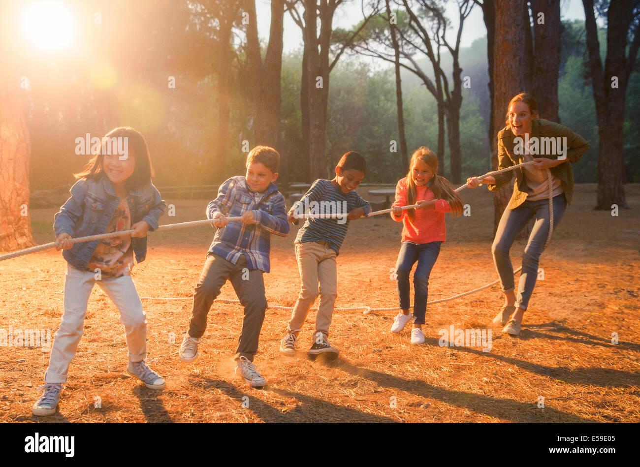 Studenti e insegnanti giocando rimorchiatore di guerra in foresta Immagini Stock