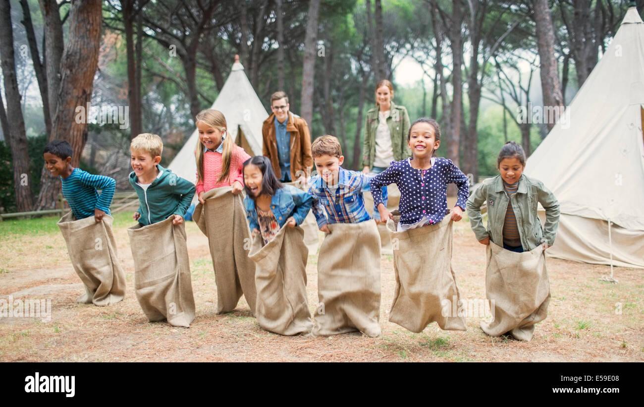 Bambini aventi il sacco gara al campeggio Immagini Stock