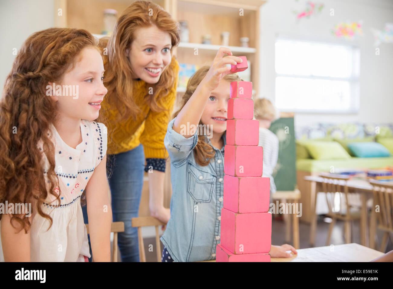 Studenti e insegnanti di blocchi di impilamento in aula Immagini Stock