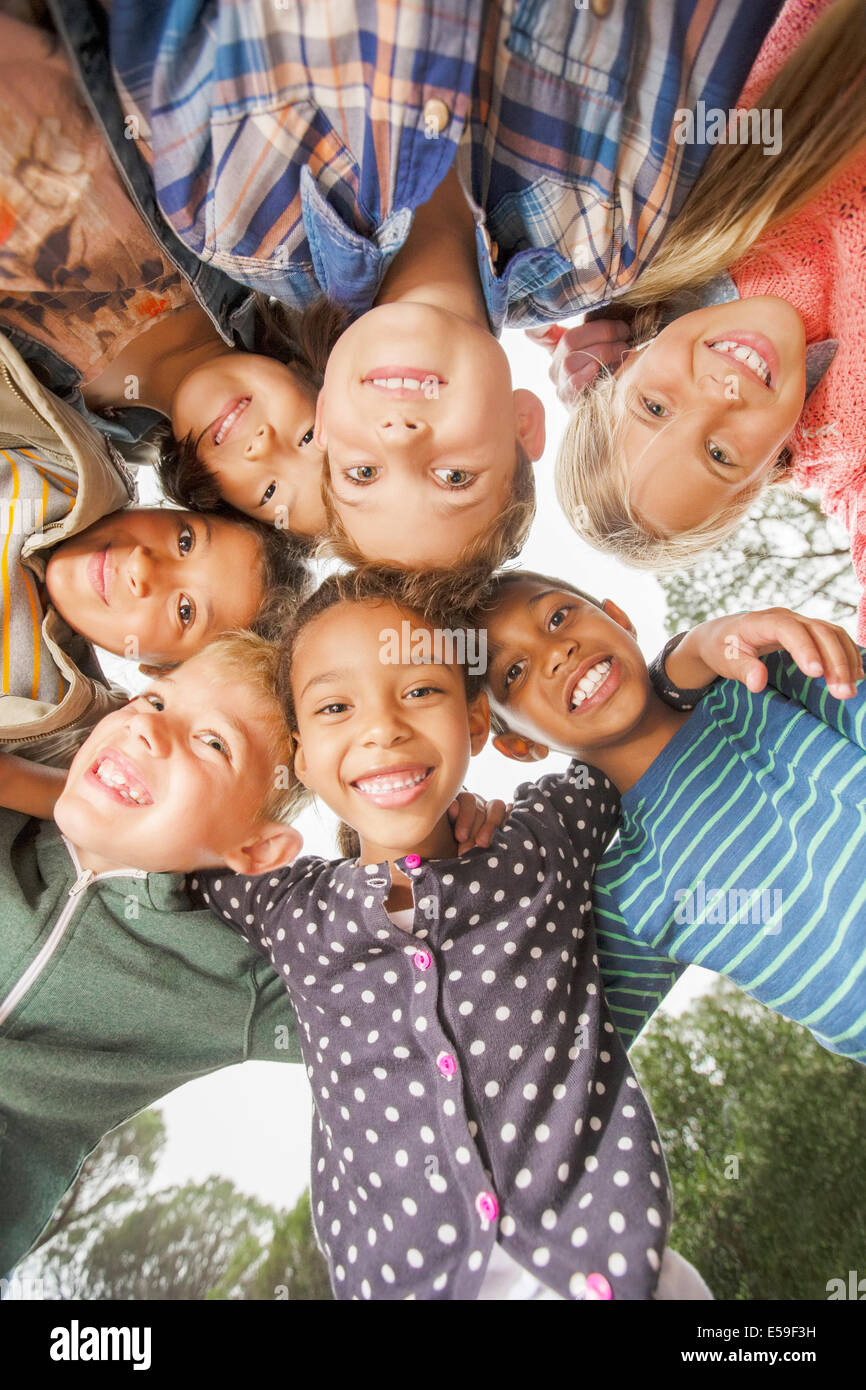 Bambini raggomitolati insieme all'aperto Immagini Stock