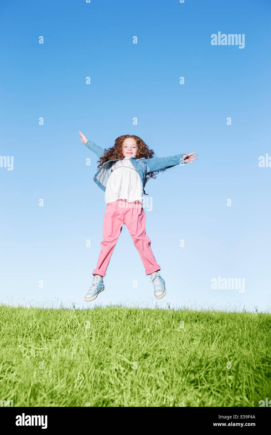 Ragazza salti di gioia sulla collina erbosa Foto Stock