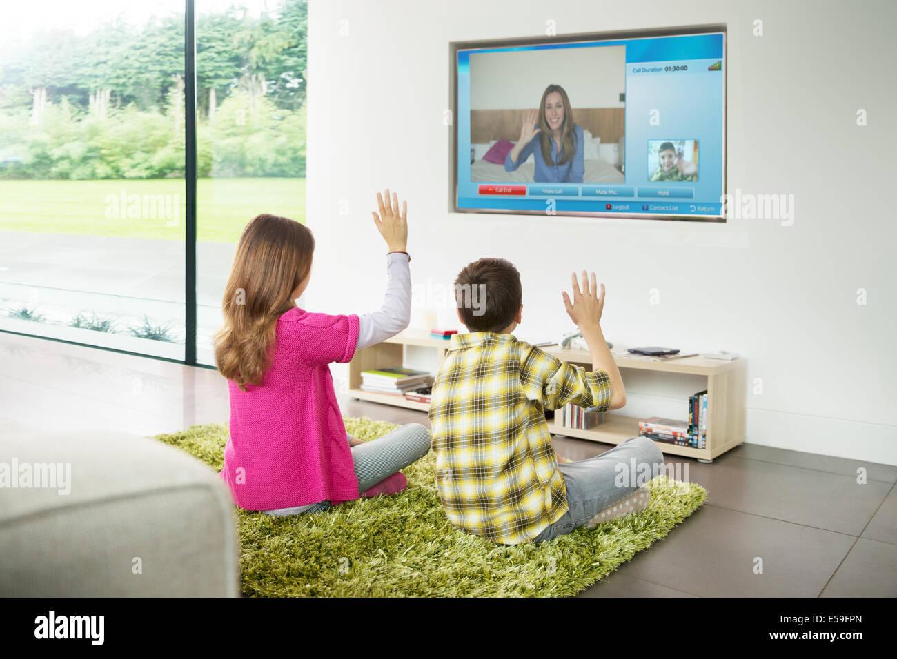 I bambini la chat video sul televisore nel soggiorno Immagini Stock