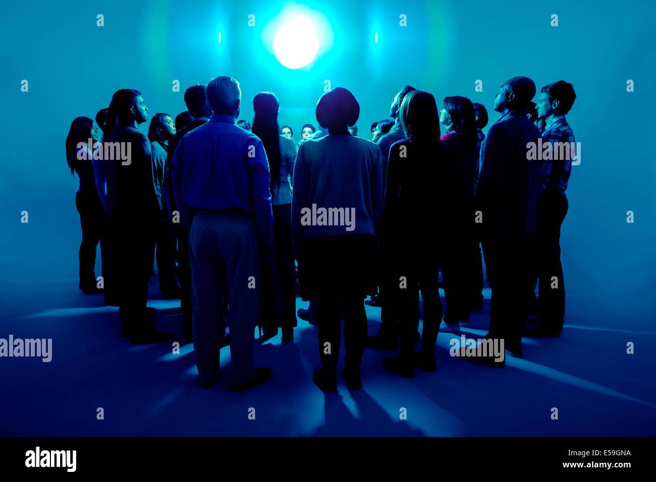 La folla in piedi intorno a una luce brillante Immagini Stock