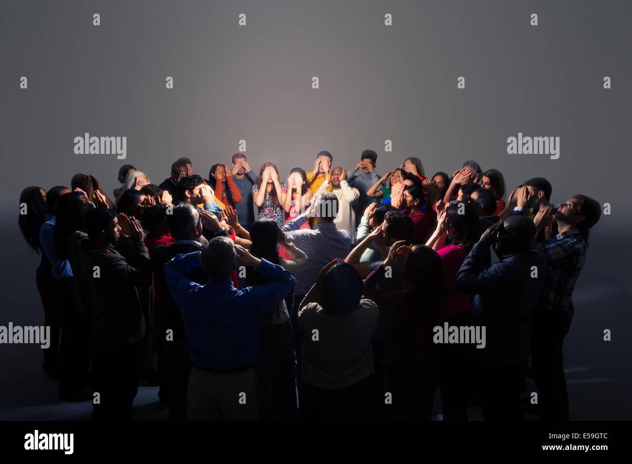 La gente di affari che copre gli occhi intorno a una luce brillante Immagini Stock