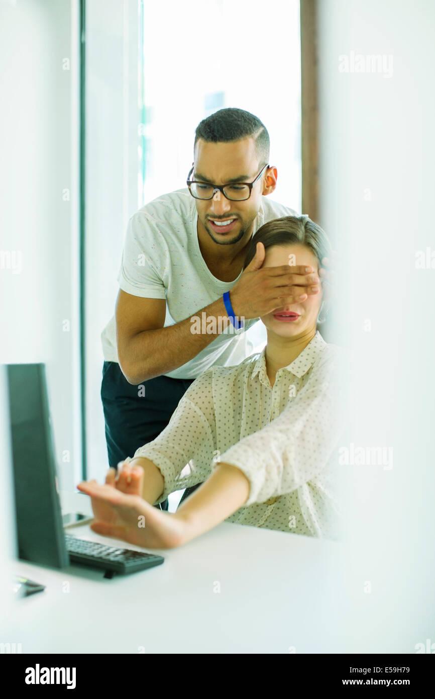 Uomo di copertura del collega agli occhi in ufficio Immagini Stock
